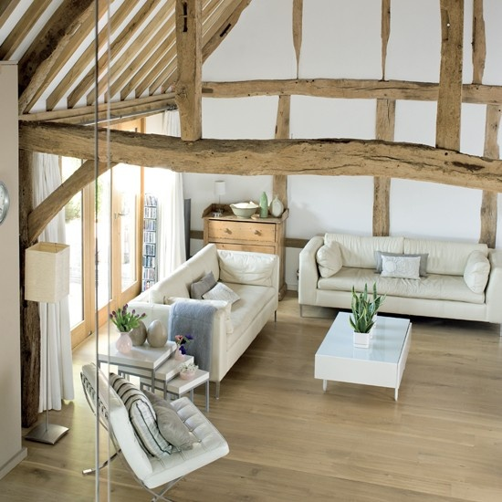 a neutral barn living room with wooden beams and pillars, with neutral seating furniture, white coffee tables, potted greenery and blooms