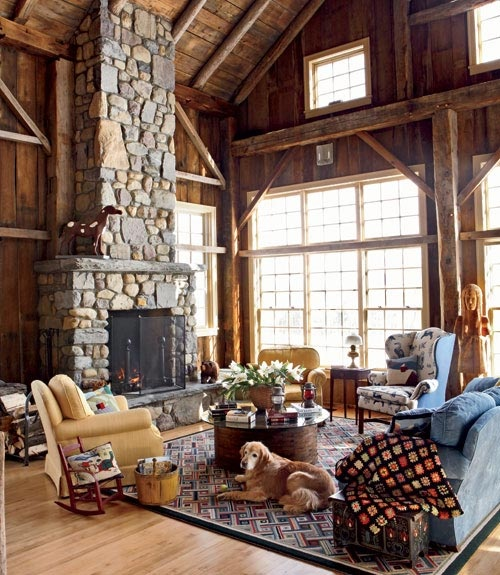 a barn living room clad with wood and with a wooden ceiling, a fireplace clad with stone, blue and yellow seating furniture, printed textiles and potted blooms