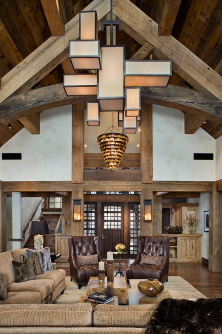 a barn living room with wooden beams and pillars, with neutral seating furniture, brown leather chairs, a stone coffee table and a very eye-catchy cube chandelier