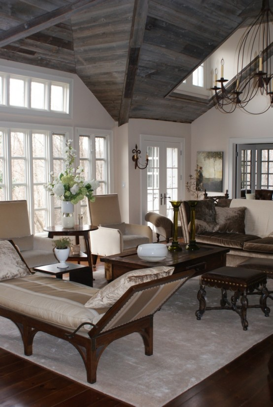 a refined barn living room with a reclaimed wood ceiling, white walls, a vintage chandelier, neutral printed furniture with dark stained legs is amazing
