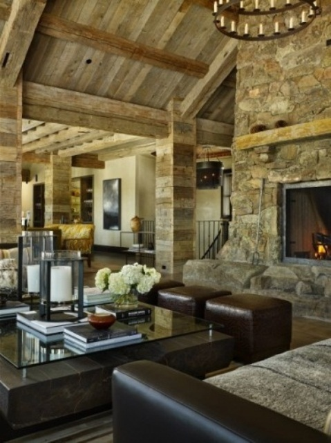 a barn living room with reclaimed wood walls and a ceiling, a fireplace clad with stone, dark leather furniture and a glass and stone coffee table is amazing