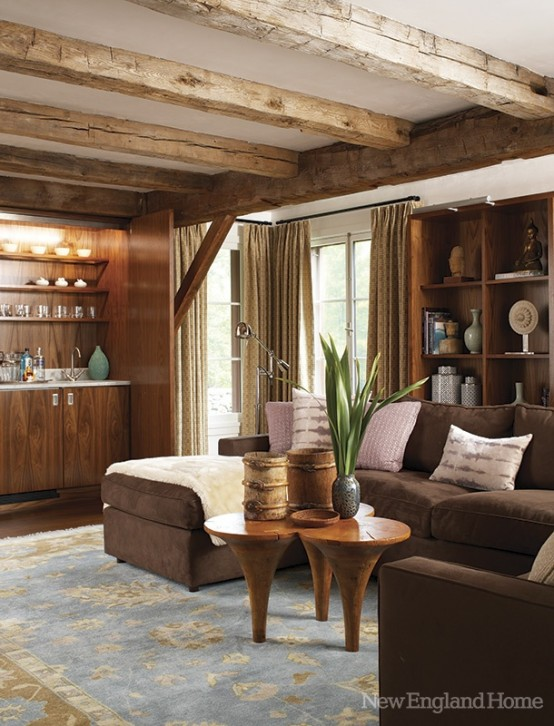 a barn living room with wooden beams, a built-in wooden bar, a brown sectional, a creative coffee table and built-in wooden shelves