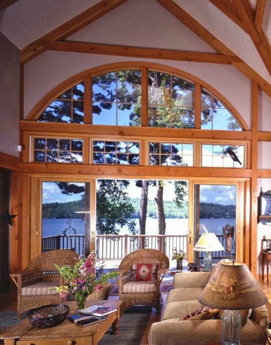 a barn living room with wooden beams and pillars, with a gorgeous view, neutral seating furniture and table lamps plus bright blooms
