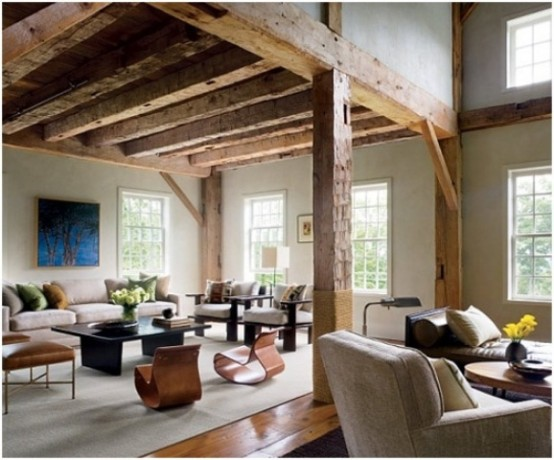 a barn living room with wooden beams and pillars, with chic contemporary furniture, neutral and dark, with low coffee tables and a bold artwork is amazing