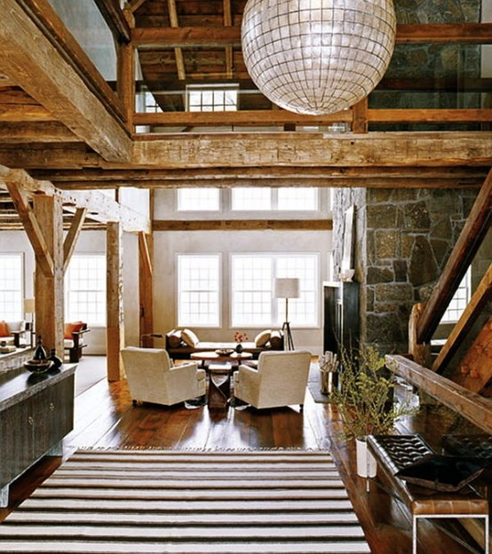 a barn living room with wooden beams and pillas, a fireplace clad with stone, neutral seating furniture and various lamps