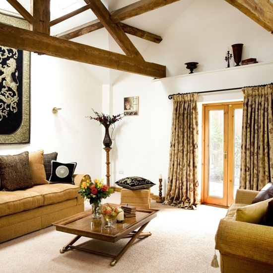 a welcoming barn living room with wooden beams, tan-colored seating furniture, bright and printed textiles, a stained wooden table and a coat of arms