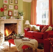 a bright red sofa, striped orange curtains and a fall-inspired gallery wall make this living room fall-like