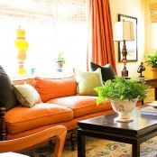a bright orange sofa and a curtain will make your living room feel liek autumn