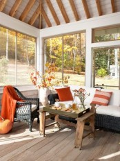 orange-colored pillows and a blanket plus some fall leaf arrangements will make your home feel cozier during this season