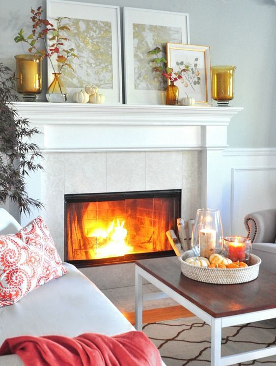 a printed pillow, a red blanket, amber glass candle holders, fall leaf arrangements