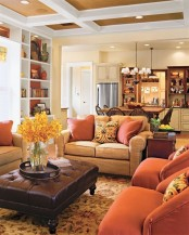 orange chairs and pillows will easily bring a fall feel to the space and a yellow bloom arrangement will help