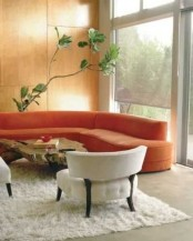 a curved orange sofa brings an autumn feeling to the space and makes it ultra-modern at the same time