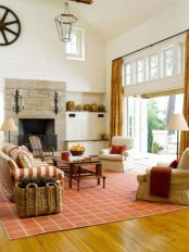 rust-colored curtaints, a rug and a striped sofa add fall aesthetics to the living room