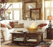 bright printed pillows, a bright floral arrangement and a basket with blooms and candles for a fall feel