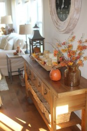 a console table with a fall leaf arrangement, a pumpkin and a wooden bowl with leaves and candles for the fall