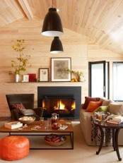 fall colored pillows, a bright orange leather ottoman and fall leaf arrangements add a fall touch to the space