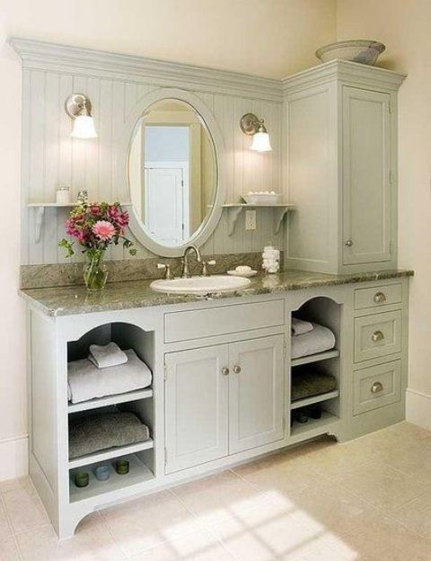 a pastel farmhouse bathroom shows off a large green grey unit that is a vanity and a storage piece at the same time