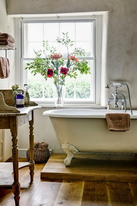 a vintage farmhouse bathroom with a clawfoot bathtub on a platform and a vintage vanity