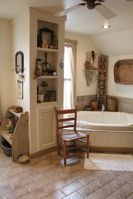 a cozy neutral farmhouse bathroom with earthy tiles on the floor and walls, a storage unit and a sunken bathtub