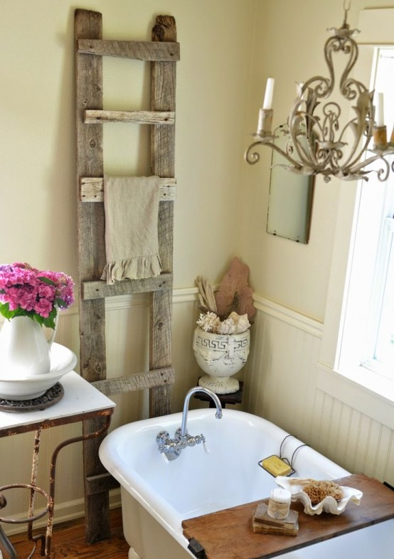 a neutral warm-colored farmhouse bathroom with sandy walls, white beadboard, a clawfoot bathtub and an old ladder to hang towels