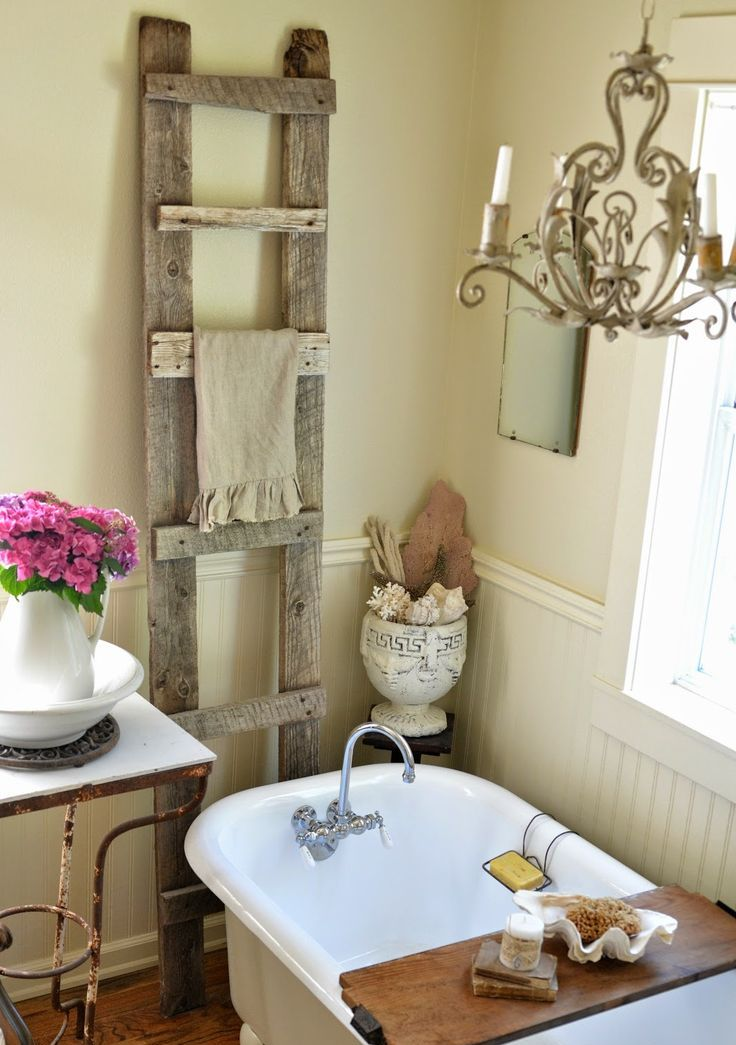 a neutral warm colored farmhouse bathroom with sandy walls, white beadboard, a clawfoot bathtub and an old ladder to hang towels
