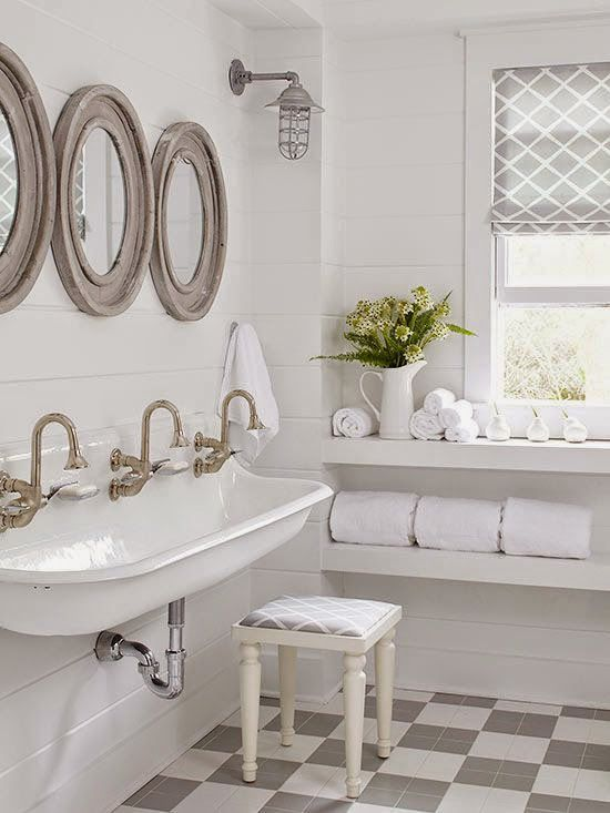 a white vintage farmhouse bathroom with wood frame round mirrors, a large sink, mosaic tiles and a window