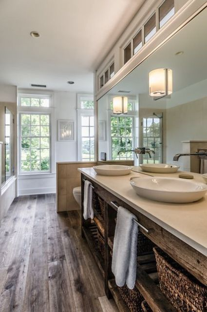 a cozy farmhouse bathroom with wooden floors, a stained wooden vanity and a half wall to divide the bathring space