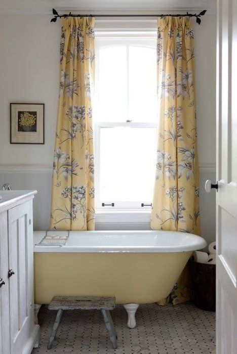 a small farmhouse bathroom with a white vanity, a yellow clawfoot bathtub, yellow printed curtains