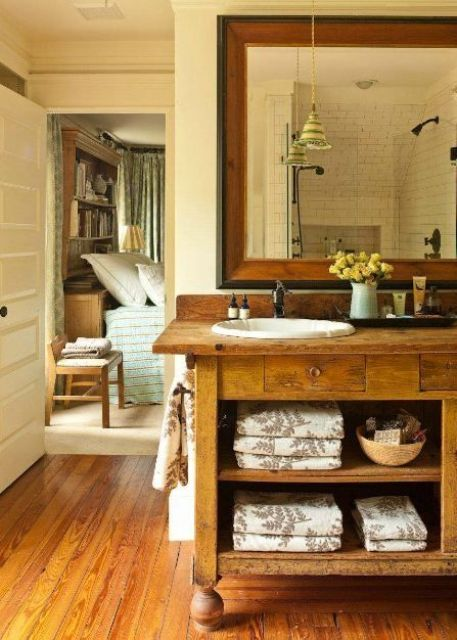 a chic farmhouse bathroom with much rich stained wood in decor, a large vintage vanity and a large mirror