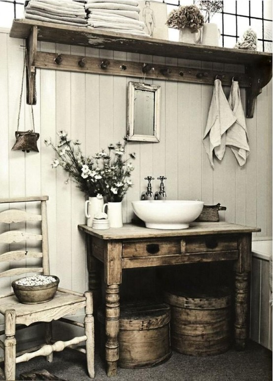 a shabby chic farmhouse bathroom with white plank walls, shabby wooden furniture, a vintage chair and round wooden boxes for storage