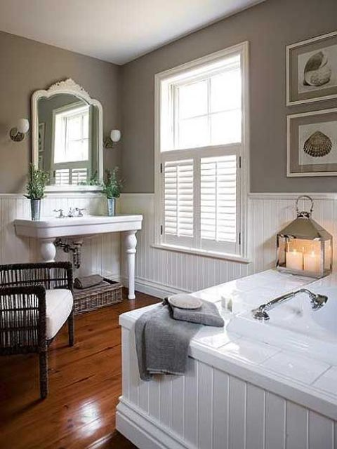 a welcoming farmhouse bathroom with white and grey walls done with beadboard, a bathtub clad with beadboard and a vintage vanity and mirror