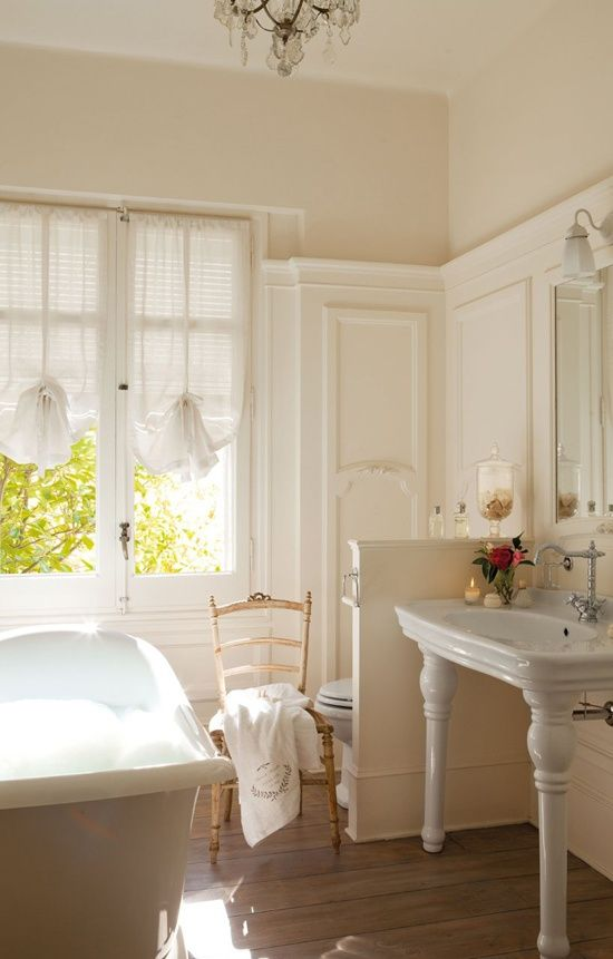 a light-filled farmhouse bathroom done in creamy shades, a clawfoot bathtub, elegant curtains-shades, a vintage vanity