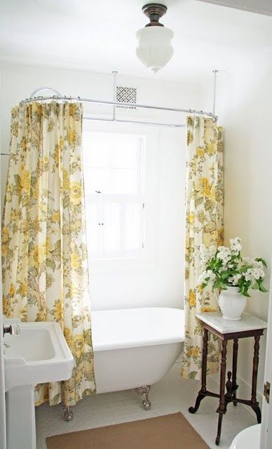 a small farmhouse bathroom with yellow printed curtains, a vintage sink and clawfoot bathtub