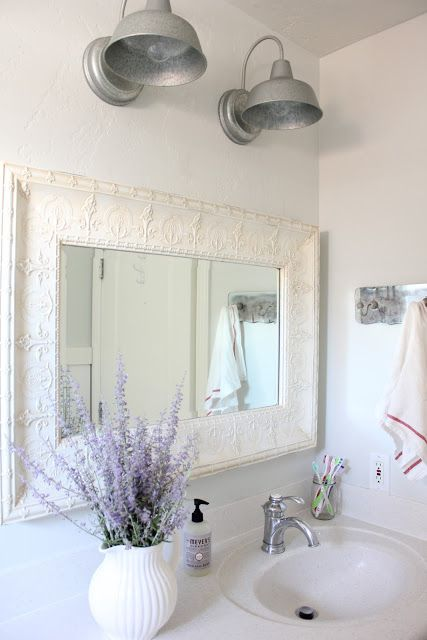 an elegant white farmhouse vanity and a vintage mirror frame plus some lavender in a vase