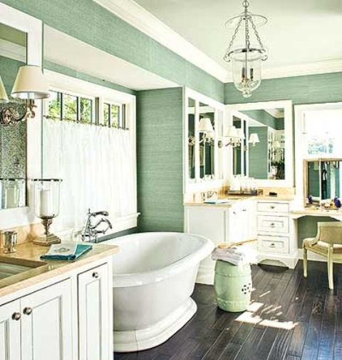 a green farmhouse bathroom with an oval tub, creamy vanities and a storage unit, a vintage chair and mirrors