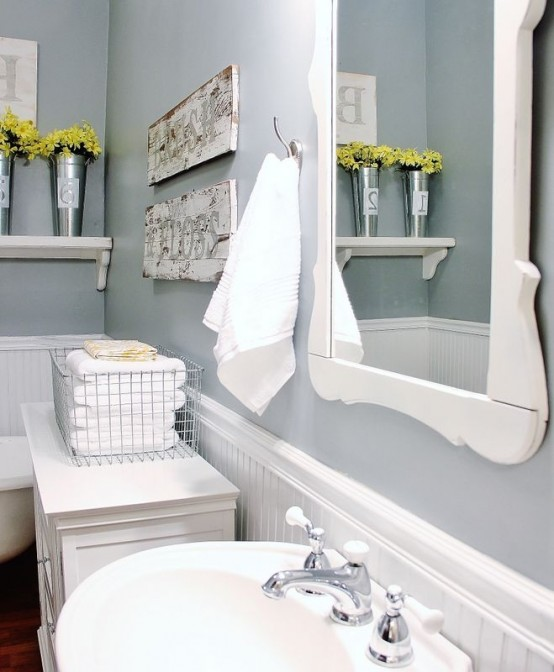 a grey and white farmhouse bathroom with white beadboard, a white sink and frame plus a vanity