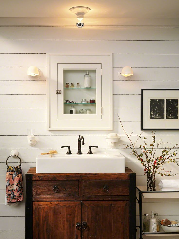 a white farmhouse bathroom with planks on the walls, a rich stained wooden vanity and a built in apothecary storage unit