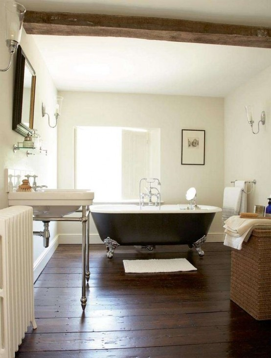 a cozy farmhouse bathroom with a dark wooden floor, a black clawfoot bathtub, a white sink and a mirror