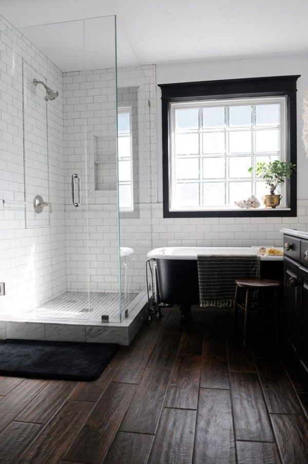 a laconic monochromatic farmhouse bathroom with a dark wooden floor, white subway tiles, a black clawfoot bathtub and a window