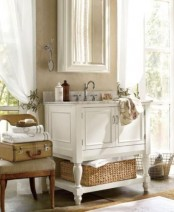 a white vintage farmhouse bathroom with a refined white vanity, white curtains and a chair with suitcases