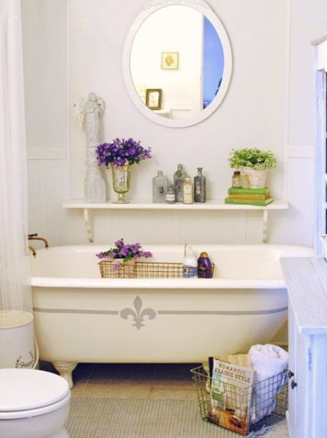 a cute farmhouse bathroom in creamy shades, a clawfoot bathtub, a rug, a shelf with potted plants and a round mirror