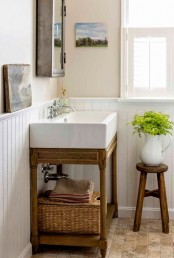 an inviting farmhouse bathroom nook with a wooden vanity, baskets, stools and artworks