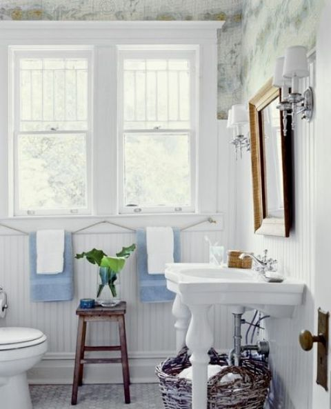a stylish farmhouse bathroom with printed wallpaper, white beadboard, a sink and a mirror in a vintage frame