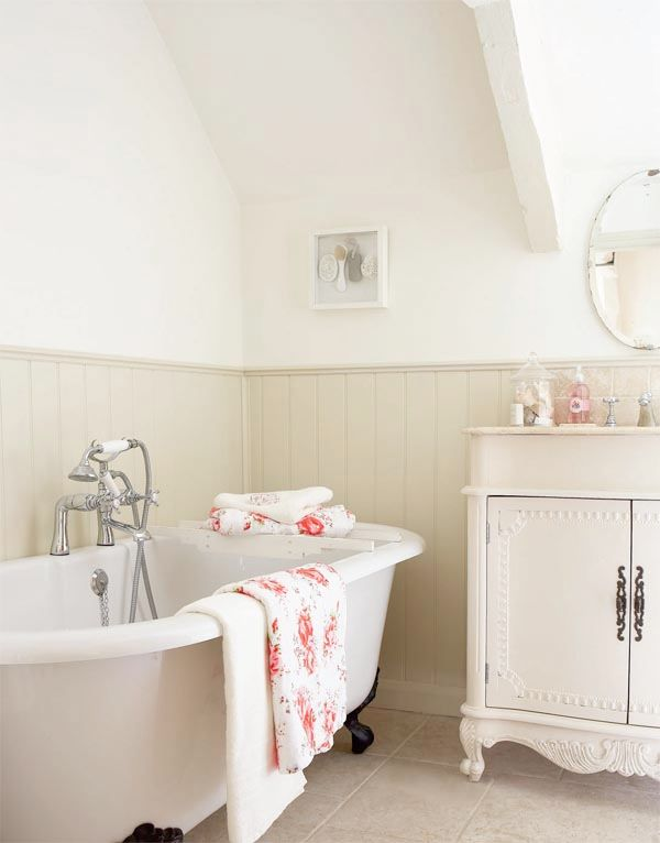 a cute and welcoming farmhouse bathroom in creamy and off white, a blush bethtub, off white beadboard and a vintage vanity