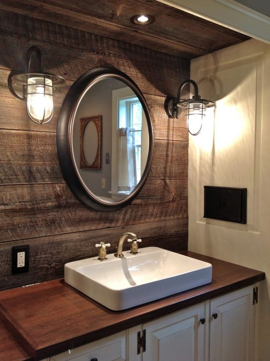 a rustic bathroom with a weathered wooden wall, wall lamps, a white vanity with a wooden top and a square sink
