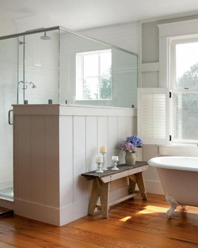 a cozy and light filled neutral farmhouse bathroom with a clawfoot bathtub, a shower partly clad with beadboard