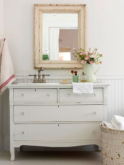 a vintage farmhouse bathroom with a white sideboard, a shabby chic frame mirror, a fabric basket for storage