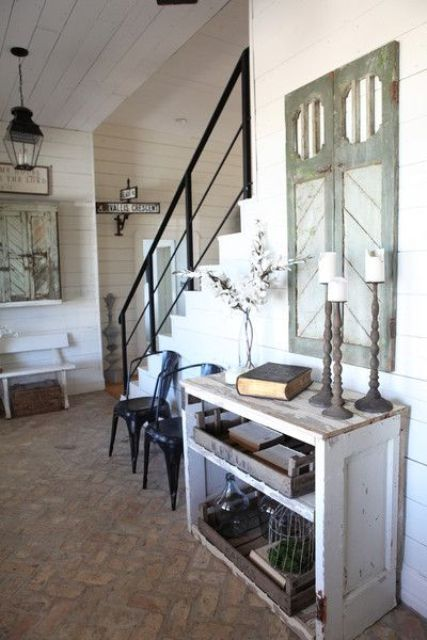 a vintage farmhouse entryway with a wooden console, a vintage shutters on the wall and pendant lamps