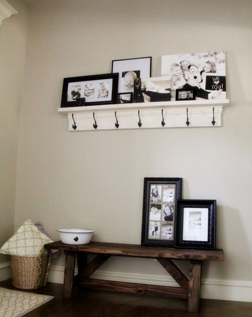 a monochromatic farmhouse entryway with a dark staiend bench, a white rack, a gallery wall with family pics on the rack