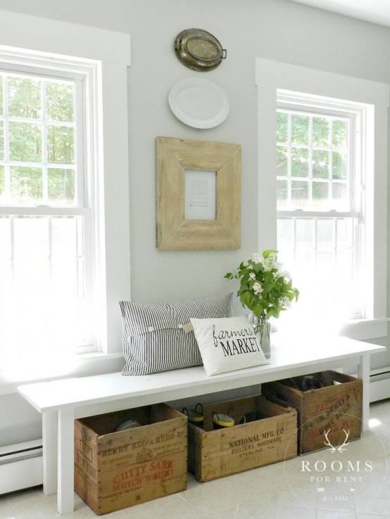 a neutral farmhouse entryway with an artwork, decorative plates, a bench, wooden boxes for storage and a striped pillow